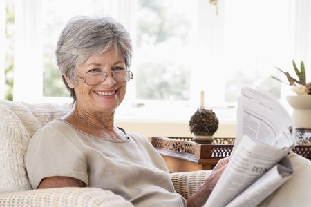 reading glasses: Woman in living room reading newspaper smiling Stock Photo