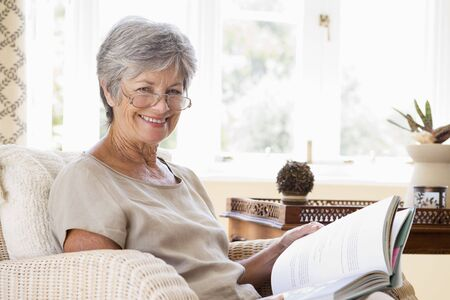 Woman in living room reading book smiling photo
