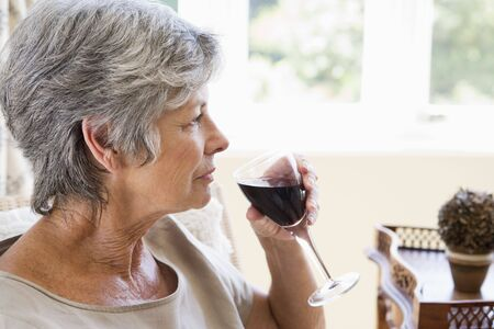 redwine: Woman in living room with glass of wine