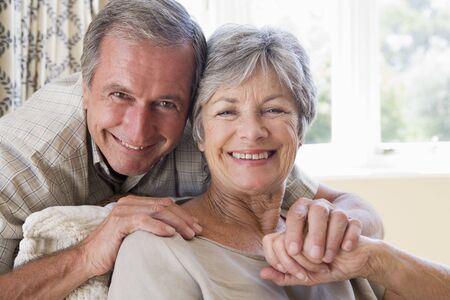 mature couple: Couple relaxing in living room smiling