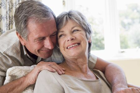 Couple relaxing in living room smiling photo