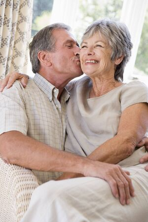 Couple relaxing in living room kissing and smiling Stock Photo - 3475022