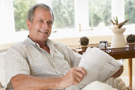 Man in living room reading newspaper smiling Stock Photo - 3461256