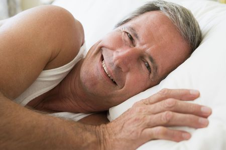 Man lying in bed smiling photo