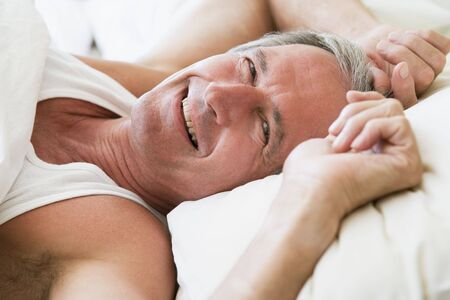Man lying in bed smiling Stock Photo - 3470809