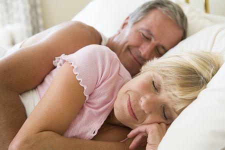 sleeping man: Couple lying in bed sleeping Stock Photo