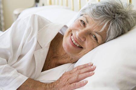 1 senior: Mujer en la cama sonriente Foto de archivo