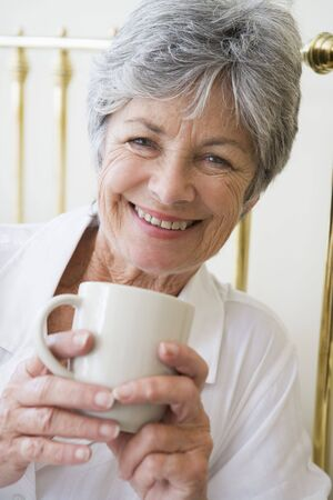 nightclothes: Woman in bedroom with coffee smiling
