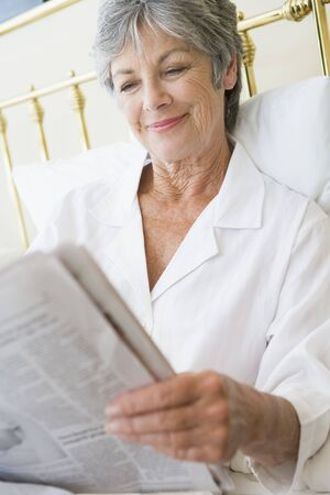 Woman in bedroom with newspaper smiling Stock Photo - 3460825