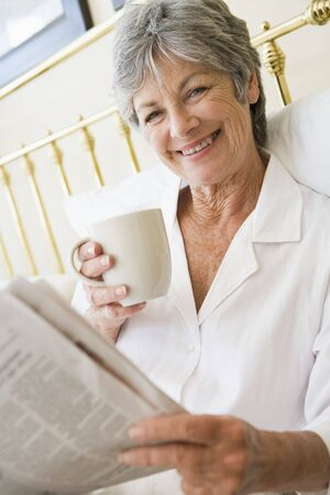 nightclothes: Woman in bedroom with coffee and newspaper smiling