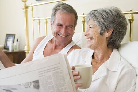 Couple in bedroom with coffee and newspapers smiling photo