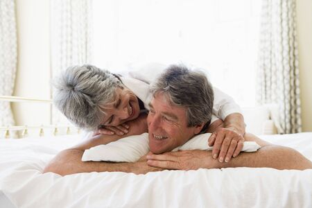 Couple relaxing in bedroom and smiling Stock Photo - 3460797