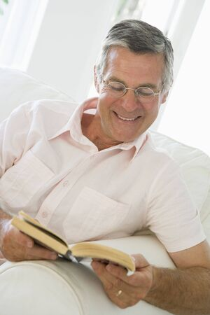 Man in living room reading book smiling Stock Photo - 3475823