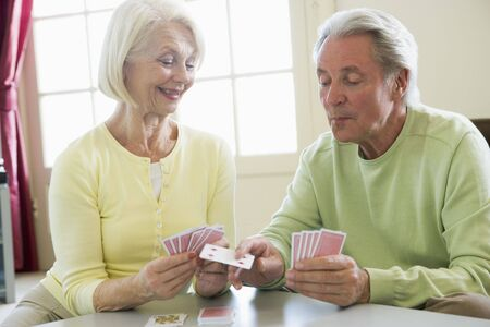 playing cards: Couple playing cards in living room smiling