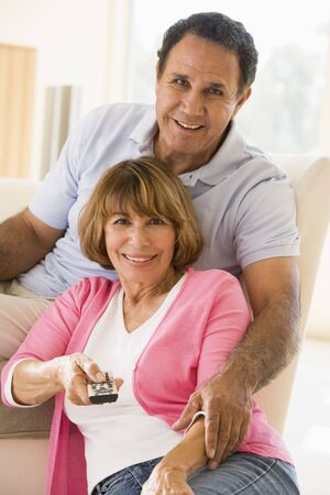 Couple in living room with remote control smiling Stock Photo - 3475863