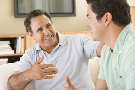 Two men in living room talking and smiling photo