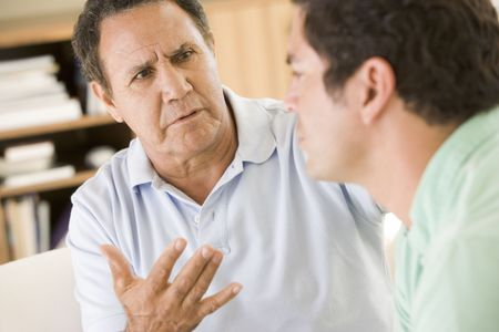 two friends talking: Two men in living room talking