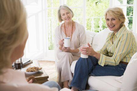 Drie vrouwen in de woonkamer met koffie glimlachende Stockfoto