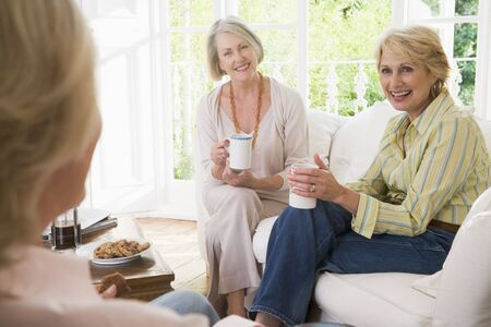 retired: Three women in living room with coffee smiling Stock Photo
