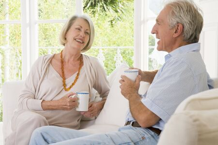 Couple in living room with coffee smiling photo