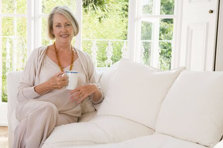 senior living: Woman in living room with coffee smiling
