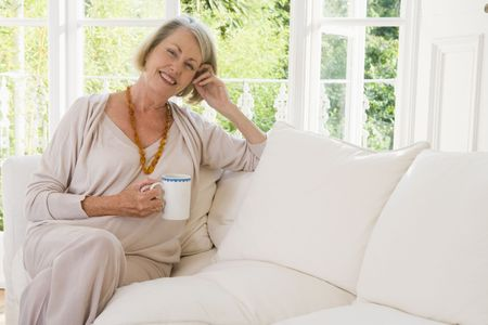 Woman in living room with coffee smiling photo
