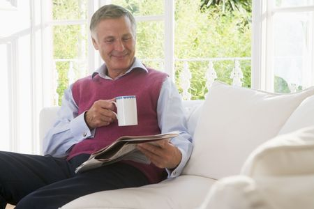 Man in living room with coffee reading newspaper smiling photo