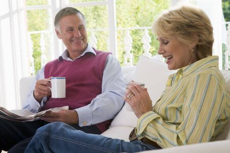 Couple in living room with coffee and newspaper smiling photo