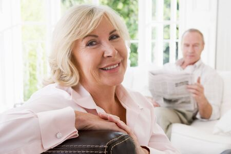 Woman in living room smiling with man in background reading newspaper photo