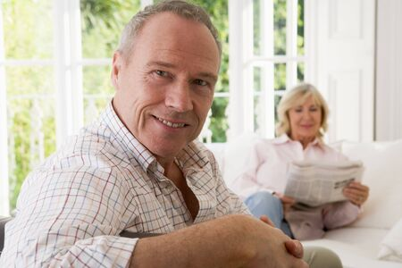 Man in living room smiling with woman in background reading newspaper photo