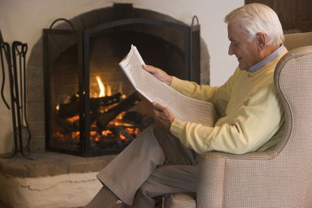 log fire: Man in living room reading newspaper Stock Photo