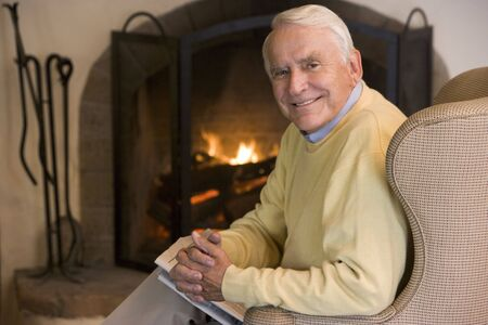 Man in living room with newspaper smiling photo