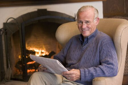 hearth and home: Man sitting in living room by fireplace with newspaper smiling