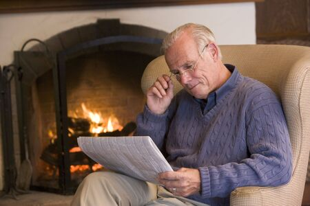 senior reading: Man sitting in living room by fireplace with newspaper