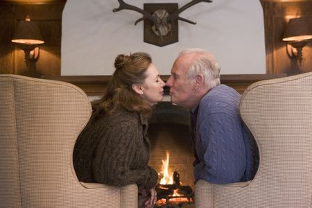 Couple sitting in living room by fireplace kissing photo