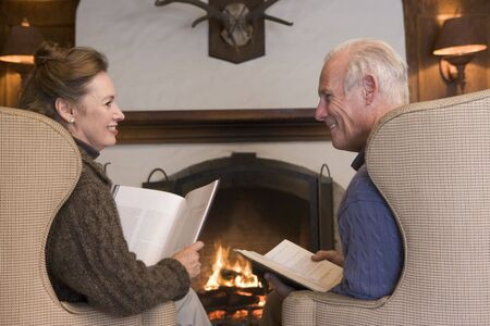Couple sitting in living room by fireplace with books smiling photo
