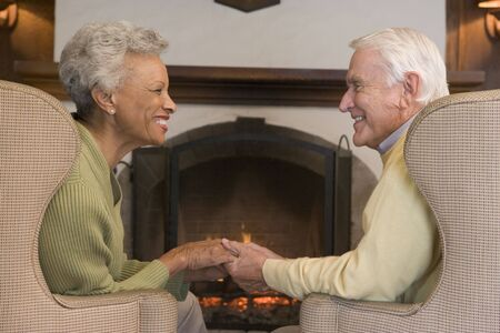 Couple sitting in living room by fireplace holding hands and smiling photo
