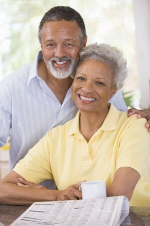 Couple relaxing with a newspaper smiling Stock Photo - 3475765