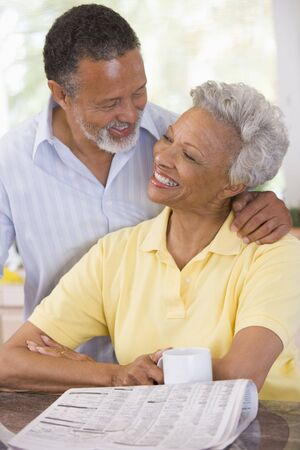 Couple relaxing with a newspaper smiling Stock Photo - 3475835