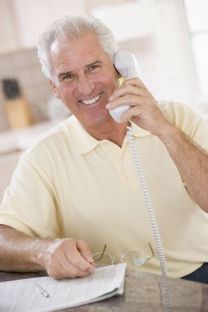 Man in kitchen on telephone smiling photo