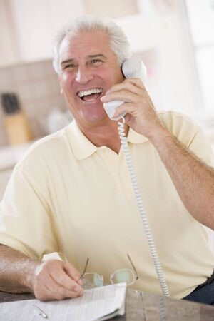 Man in kitchen on telephone laughing photo