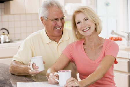 Couple in kitchen with coffee smiling photo