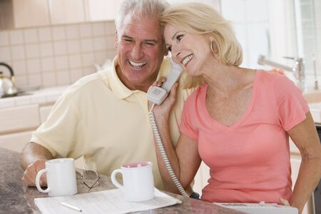 Couple in kitchen with coffee using telephone together and smiling photo