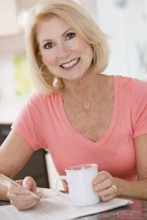 Woman in kitchen with coffee and newspaper smiling photo