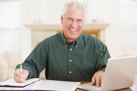 Man in dining room with laptop and paperwork smiling photo