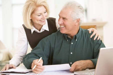 senior reading: Couple in dining room with laptop and paperwork smiling Stock Photo