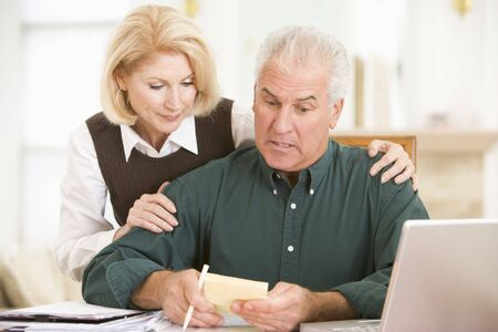 Couple in dining room with laptop and paperwork looking worried photo