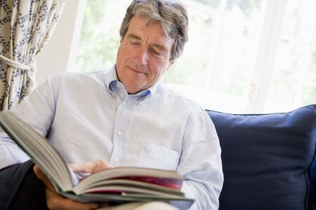 Man relaxing with book in living room photo