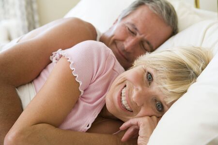 Couple lying in bed together smiling photo