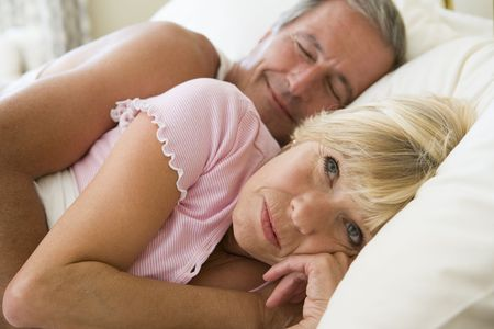 Couple lying in bed together photo